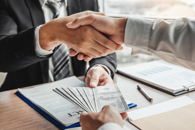 Businessman shaking hands giving dollar bills to business manager Premium Photo