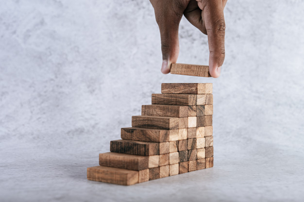 Stacking wooden blocks is at risk in creating business growth ideas. Free Photo
